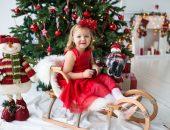 Девочка сидит на санях у новогодней ёлки