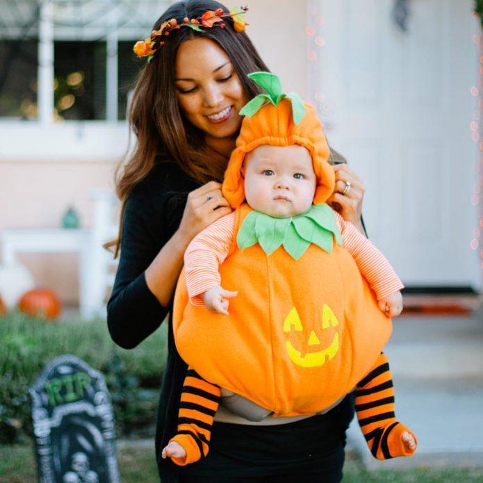 Маленький ребенок в костюме тыквы на Хэллоуин