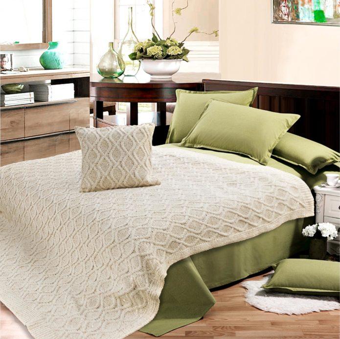 Вязаный плед белого цвета на кровати