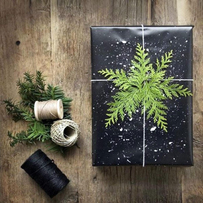 Эффектная упаковка подарка из черной бумаги с хвойными веточками