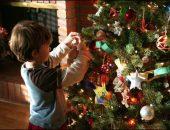 Ребенок наряжает елку
