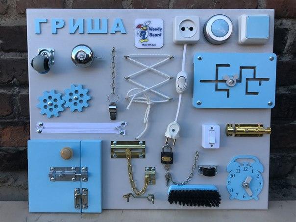 Бизиборд с голубыми элементами и надписью Гриша