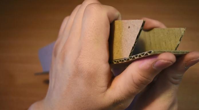 Разрезанные части картона в руках