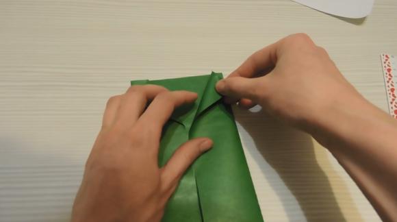 Отогнутые верхние уголки листа зелёной бумаги