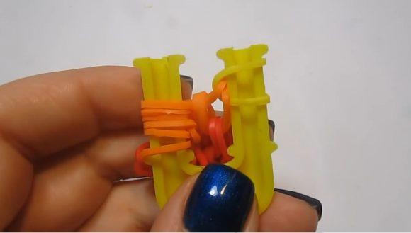 Петли из красных и оранжевых резинок на жёлтой рогатке