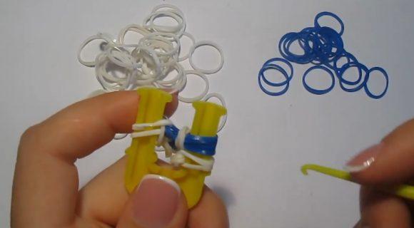 Плетение браслета из белых и синих резинок на жёлтой рогатке