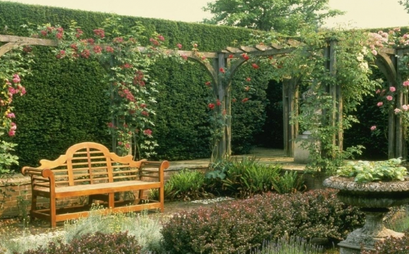 Садовая лавочка в окружении живых заборов