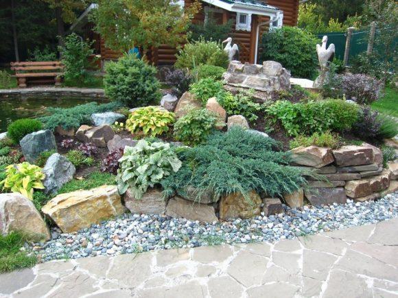 Садовая скамейка рядом с альпинарием