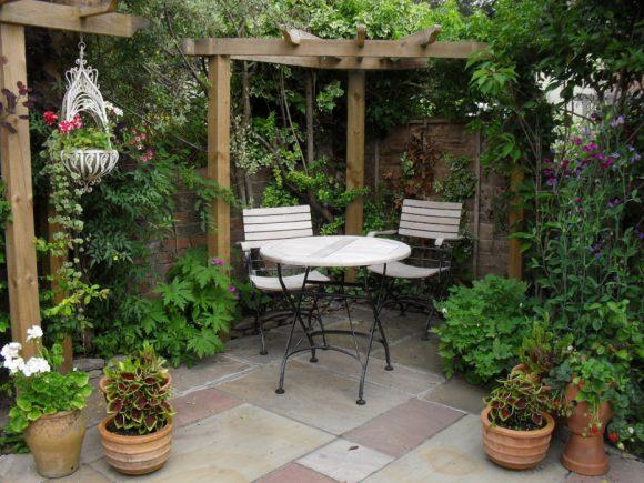 Зона отдыха в саду, украшенная цветами в кашпо и вазонах