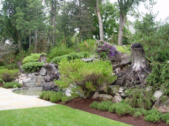 Рутарий на берегу маленького водоёма в саду пейзажного дизайна