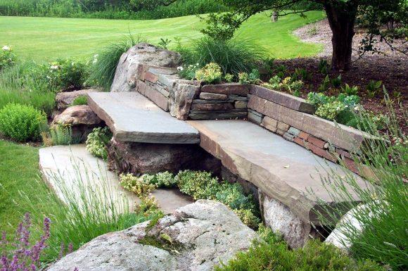 Каменная скамейка в саду природного дизайна