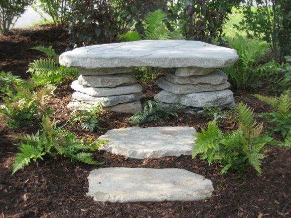 Скамья из камней в саду пейзажного дизайна