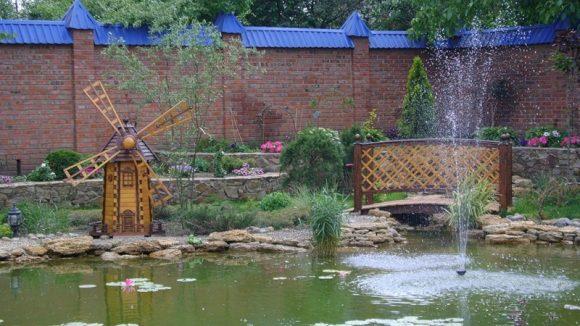 Декоративная мельница у водоема на участке