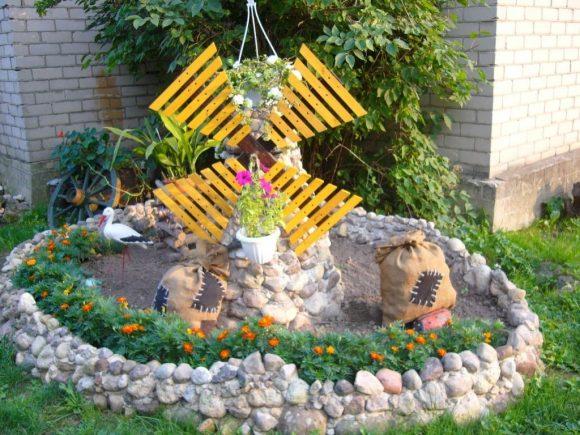 Декоративная мельница у цветника в саду