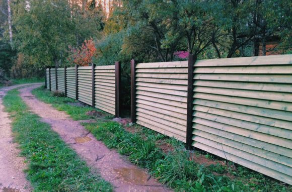 Деревянный забор с металлическими столбами