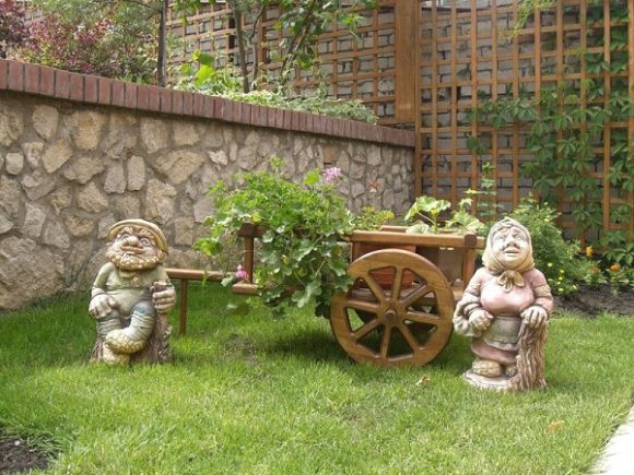 Эффектная клумба с деревянными скульптурами
