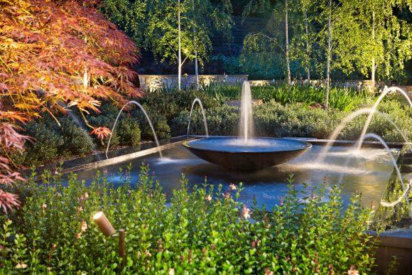 Эффектно подсвеченный фонтан в саду