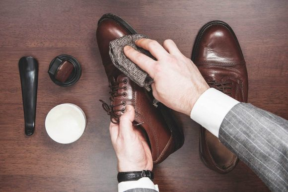 Мужчина протирает ботинки