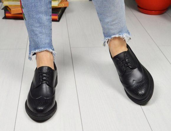Девушка в джинсах и черных лоферах
